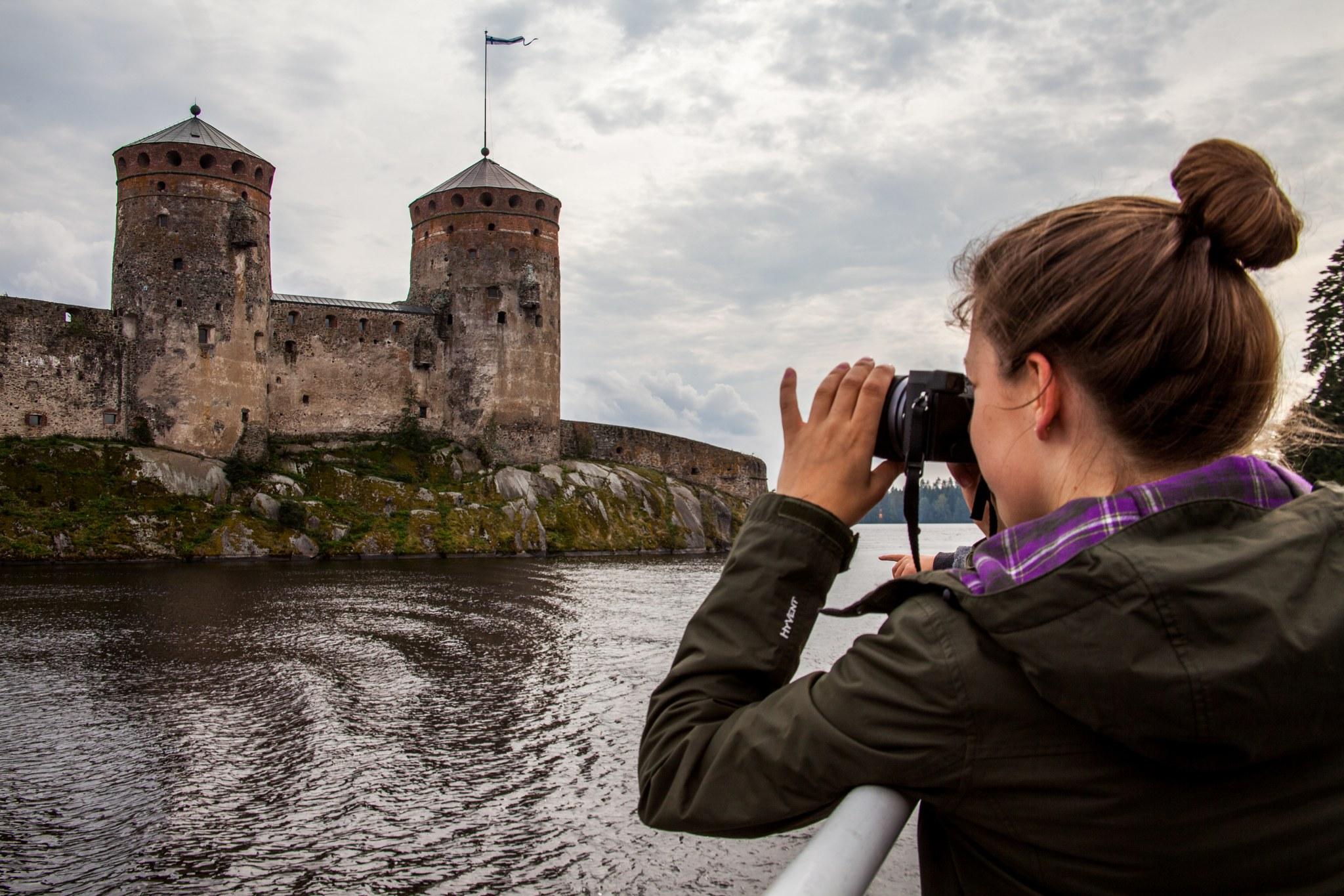 Nainen kuvaa Olavinlinnaa